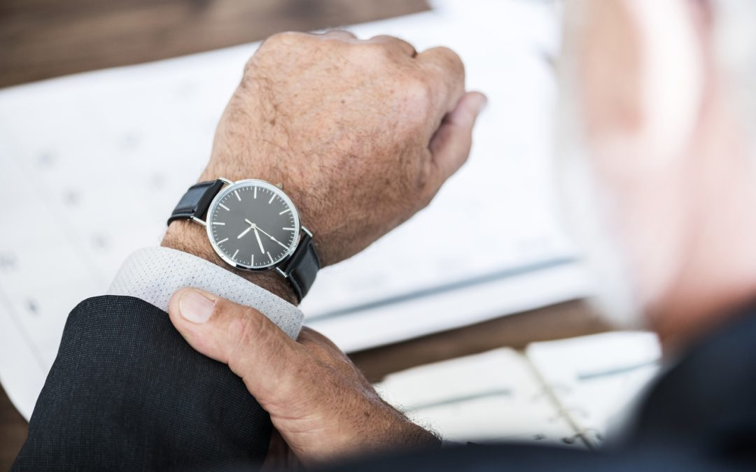 older man looking at watch on wrist