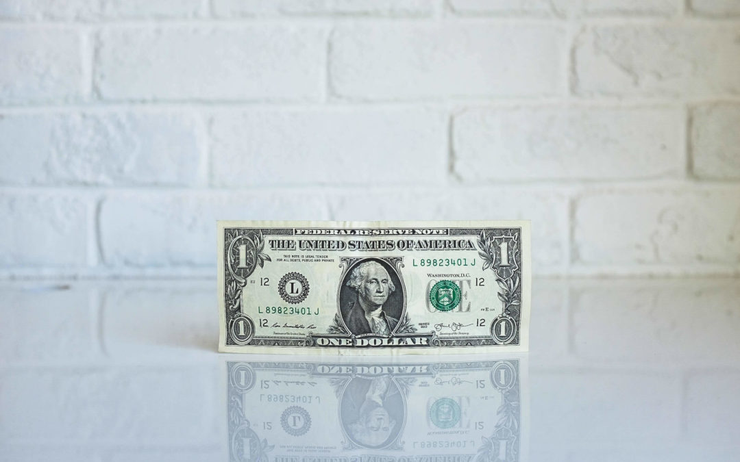 dollar on counter with white brick wall