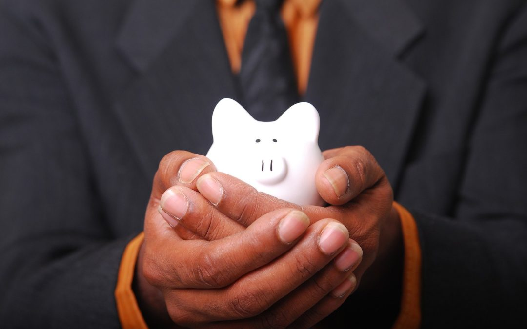 Man holding small piggy bank in hands